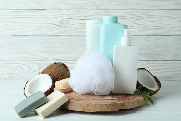 Cosméticos para banho e coco em fundo branco de madeira