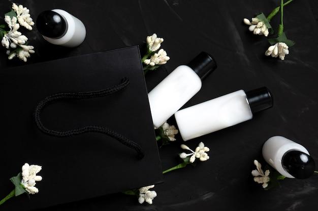 Cosméticos para cuidados com o corpo em pequenos potes em fundo escuro com saco de papel e flores brancas