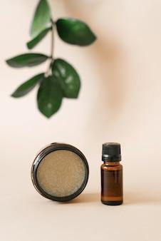 Cosméticos vegetais para cuidados com o corpo em salões de beleza. garrafa e pote com óleos em um fundo bege com folhas de zamiokulkas verdes