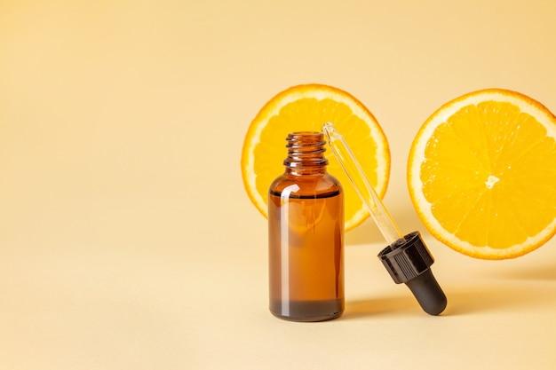 Cosméticos vitamínicos em frasco de vidro contra fatias de laranja em fundo amarelo