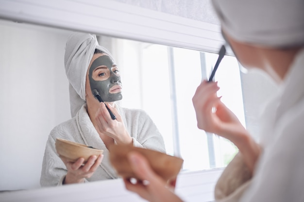 Cosmetologia, cuidados com a pele, tratamento de rosto, spa, conceito de beleza natural. bela mulher sorridente em casa em roupão com uma toalha, aplicar a máscara de argila facial contra acne para rejuvenescer a pele problemática