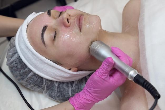 Cosmetologia de hardware, a garota está fazendo terapia de microcorrentes para o rosto.