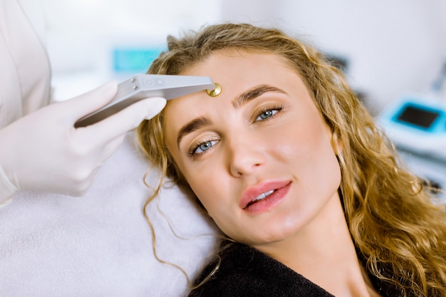 Cosmetologia de hardware. closeup retrato do rosto de mulher jovem e bonita loira recebendo procedimento de microdermoabrasão em um salão de beleza ou clínica.