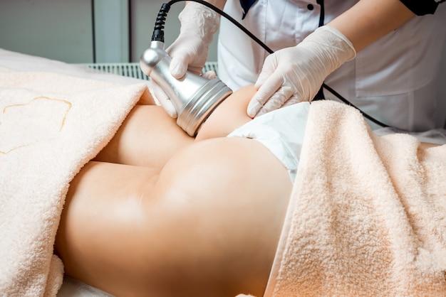 Cosmetologia de hardware. cuidados com o corpo. tratamento de spa. tratamento de contorno corporal por cavitação por ultrassom. mulher recebendo terapia anti-celulite e anti-gordura no salão de beleza.