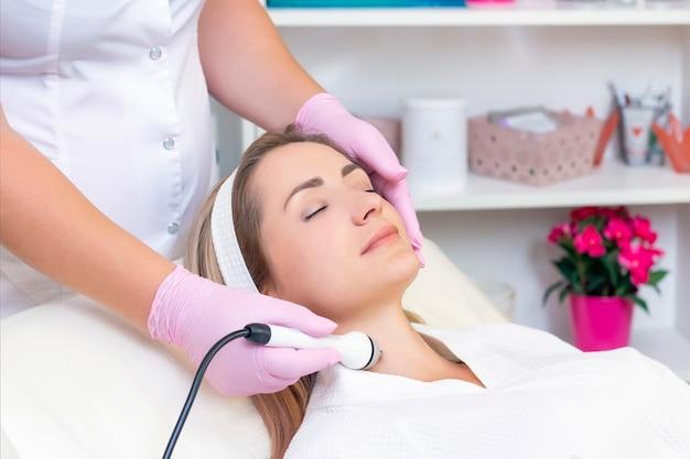 Cosmetologia de hardware. feche a foto de uma linda jovem com os olhos fechados, recebendo o procedimento de levantamento de rf no salão de beleza.