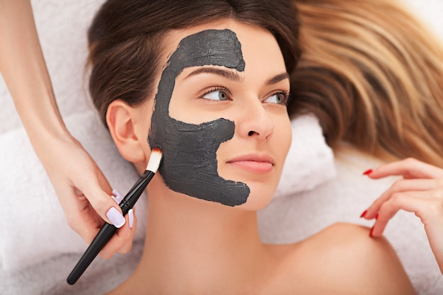 Cosmetologia de hardware. imagem do close up da jovem mulher bonita com máscara de creme em uma sala de estar de beleza.