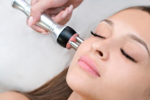 Cosmetologia de hardware. jovem mulher recebendo rf procedimento de levantamento de rosto em salão de beleza.