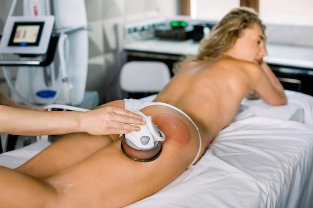Cosmetologia de hardware, procedimento de massagem a vácuo no centro médico de beleza. close-up de jovem recebendo terapia de degustação anti-celulite.