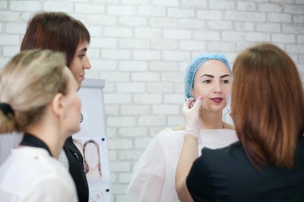 Cosmetologia decorativa. esteticistas femininas examinando o rosto da senhora antes do procedimento de cuidados com a pele.