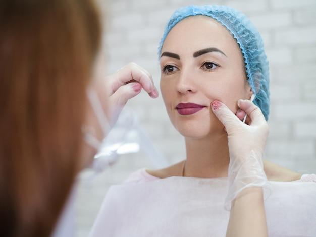 Cosmetologia decorativa. maquiagem labial definitiva. esteticista feminina, examinando o rosto de senhora.