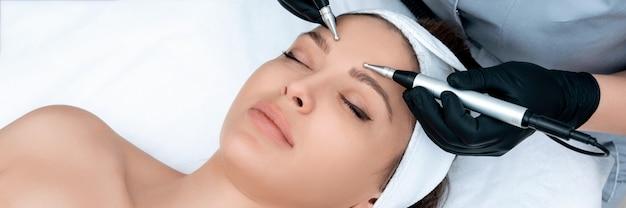 Cosmetologia. mulher bonita na clínica de spa, recebendo tratamento facial elétrico estimulante do terapeuta. close do rosto feminino jovem durante terapia de microcorrente