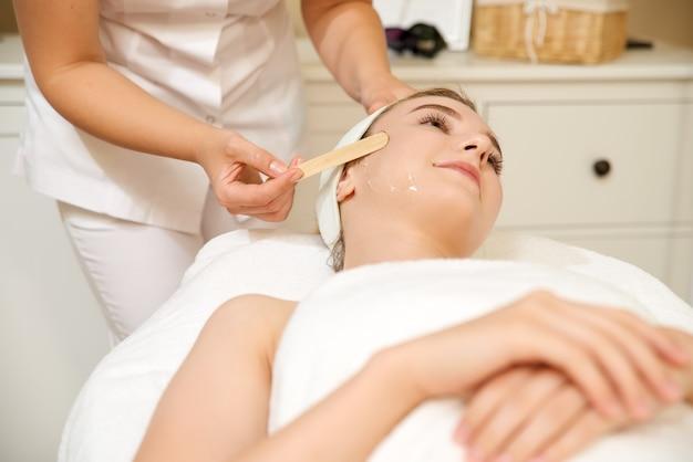 Cosmetologia. mulher bonita, recebendo procedimento de depilação a laser no salão de beleza.