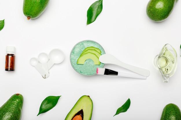Cosmetologia para cozinhar, aplicar a máscara facial. abacates, folhas, máscara facial de abacate, espátula, pincel, colheres medidoras, óleo essencial no fundo branco. cuidados com a pele, cosmético rejuvenescedor nutritivo