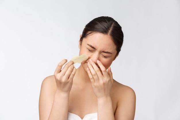 Cosmetologia. retrato do modelo asiático feminino bonito com máscara no nariz. closeup de mulher jovem e saudável com pele macia pura e maquiagem natural fresca.