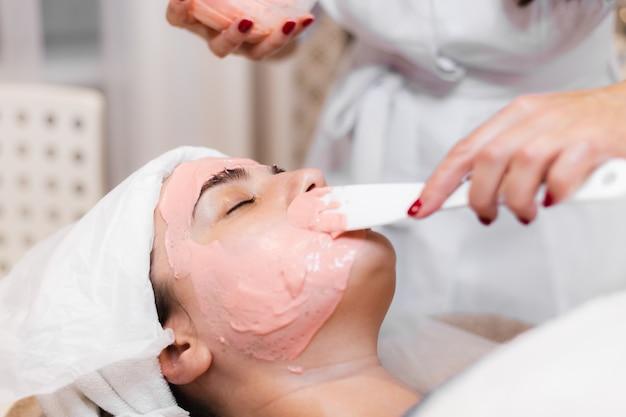 Cosmetologista aplica máscara de alginato com espátula no rosto da mulher.
