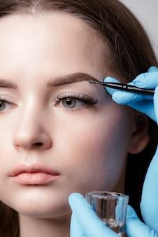 Cosmetologista aplicando maquiagem definitiva na tatuagem de sobrancelhas e sobrancelhas