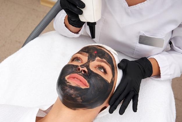 Cosmetologista aplicando máscara preta no rosto de uma mulher bonita para casca de carbono