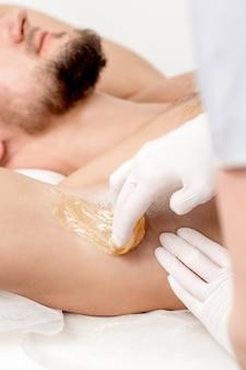 Cosmetologista aplicando pasta de cera na axila masculina