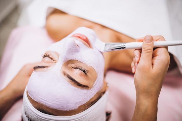 Cosmetologista aplicar máscara no rosto do cliente em um salão de beleza