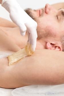 Cosmetologista aplicar pasta de cera na axila masculina