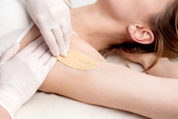 Cosmetologista aplicar pasta de cera na axila