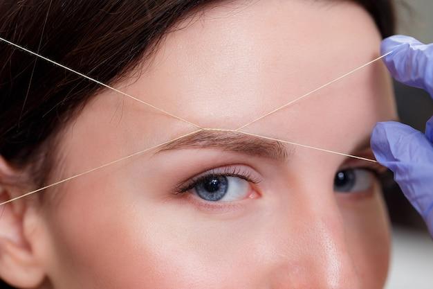 Cosmetologista arranca as sobrancelhas do cliente por fio. fechar-se