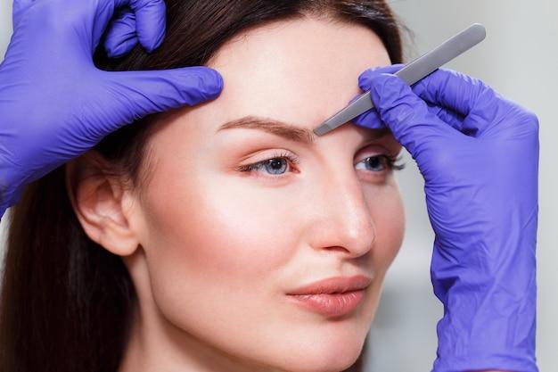 Cosmetologista arranca as sobrancelhas do cliente por uma pinça. fechar-se