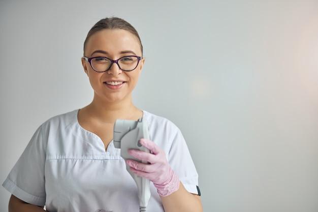 Cosmetologista charmosa em luvas esterilizadas olhando para a câmera e sorrindo enquanto segura um dispositivo de depilação a laser e rejuvenescimento da pele