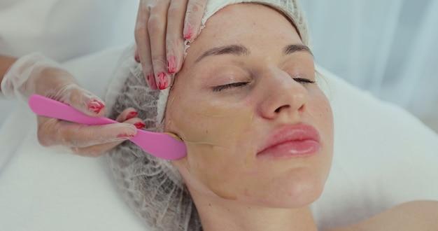 Cosmetologista closeup aplicando máscara facial com pincel para rosto de mulher bonita deitada na mesa de massagem no centro de spa.