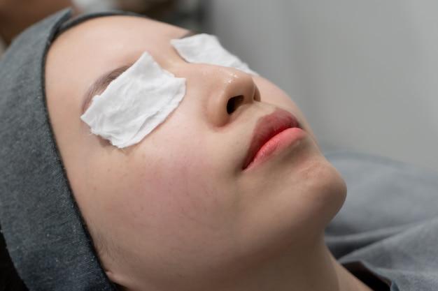 Cosmetologista coloca um curativo no rosto. preparação rosto pele antes de aplicar uma máscara rejuvenescedora em um salão de beleza.