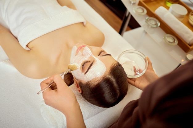Cosmetologista coloca uma máscara de creme no rosto da menina no spa s