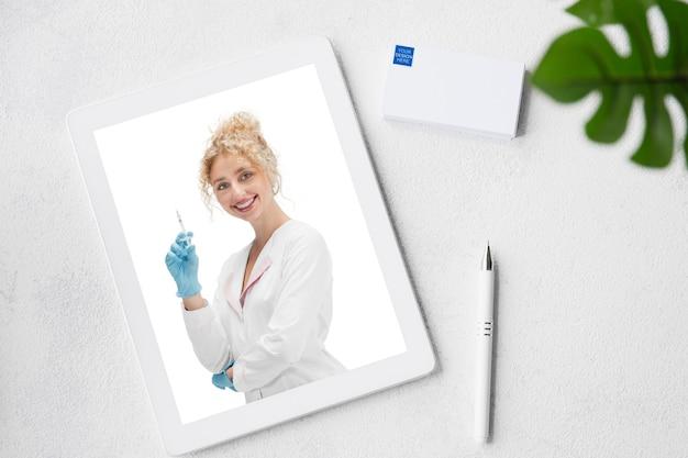 Cosmetologista com agulha. tablet com promoção on-line na web de salão de beleza spa, cosméticos, beleza e autocuidado. copyspace para anúncio. vista superior do local de trabalho. dispositivos e gadgets, conceito de tecnologia.