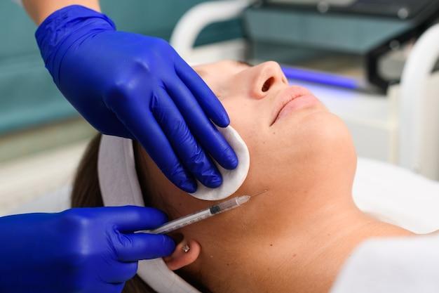 Cosmetologista com as mãos em luvas azuis segurando uma seringa com agulha e botox líquido de enchimento e almofada de algodão