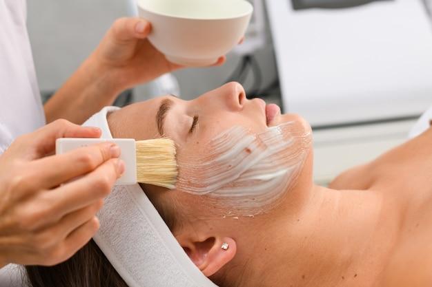 Cosmetologista com as mãos segurando uma tigela com máscara facial de creme