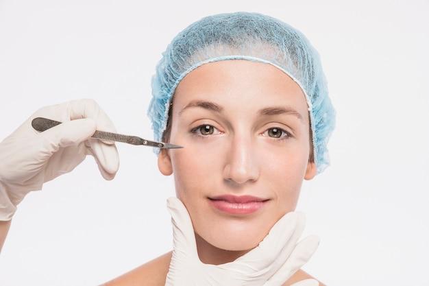 Cosmetologista com bisturi perto do rosto de mulher