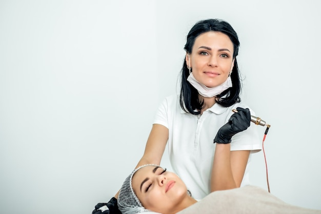 Cosmetologista com paciente durante o procedimento de extensão de cílios em pé sobre fundo branco, copie o espaço.