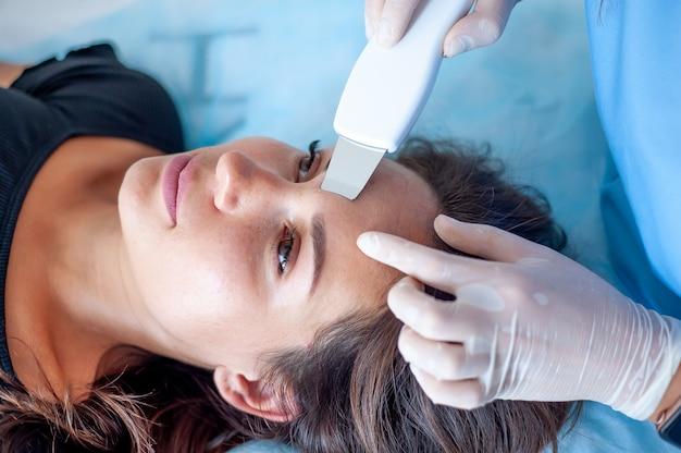 Cosmetologista com um paciente durante procedimentos faciais em uma clínica estética e estética moderna. um paciente recebe uma massagem facial elétrica. rejuvenescimento da pele e suavização de rugas.