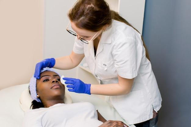 Cosmetologista de mulher no trabalho. esteticista, limpar a pele das pálpebras com cuidado. jovem mulher africana, deitado no sofá na sala. cosmetologia e cuidados com a pele