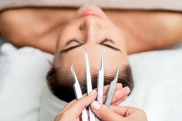 Cosmetologista detém pinças para extensões de cílios.