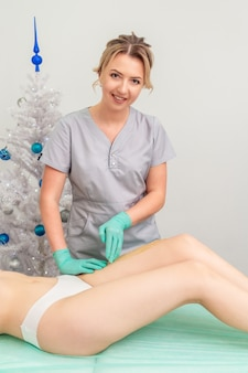 Cosmetologista em luvas de aplicação de pasta para depilação com açúcar nas pernas de mulher jovem. cera com desconto de natal