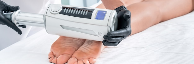 Cosmetologista em luvas de borracha, fazendo terapia de endosferas nos pés femininos