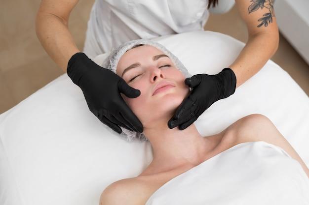 Cosmetologista esfregando ácido hialurônico no rosto de jovem