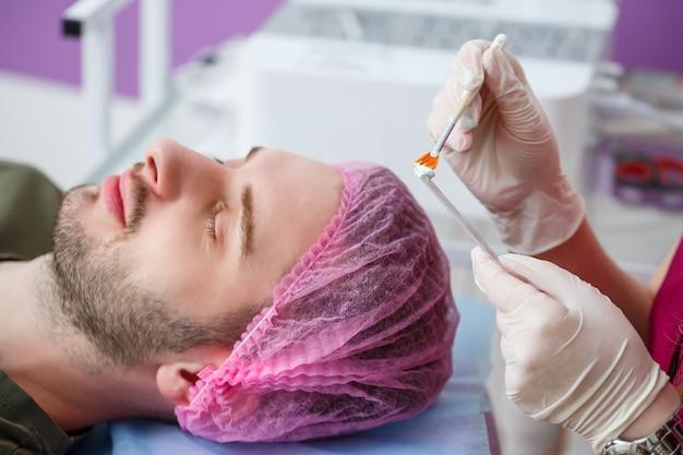 Cosmetologista está aplicando máscara hidratante branca no rosto do homem, usando a escova na clínica de beleza, closeup de rosto. conceito da indústria da beleza. cara está deitado no sofá. mulher esteticista fazendo procedimento de spa.