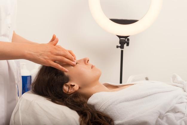 Cosmetologista está fazendo uma massagem facial para uma jovem.
