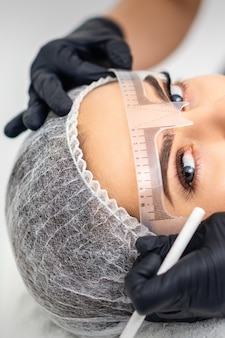 Cosmetologista está medindo com régua as sobrancelhas de uma jovem mulher branca antes da tatuagem de maquiagem definitiva