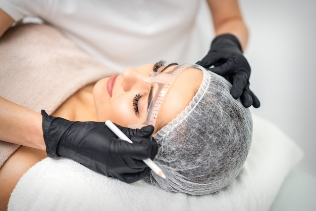 Cosmetologista está medindo com régua as sobrancelhas de uma jovem