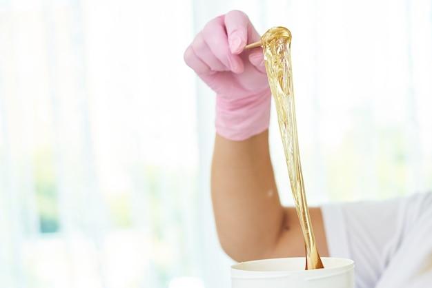 Cosmetologista está tirando pasta de açúcar.