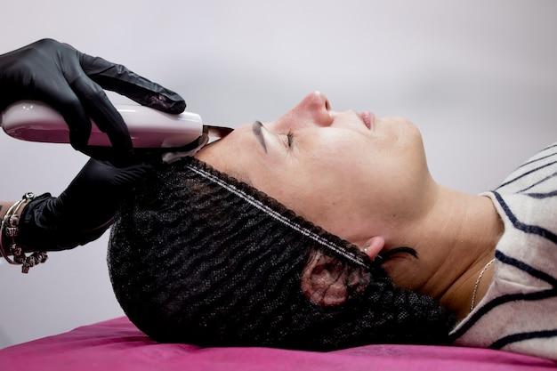 Cosmetologista, esteticista fazendo tratamento facial com espátula ultrassônica para mulher jovem, tratamento com purificador de pele do rosto com espátula ultrassônica, procedimento de limpeza facial em salão de beleza.