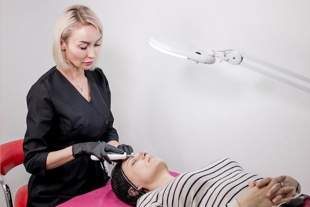 Cosmetologista, esteticista fazendo tratamento facial com espátula ultrassônica para mulher