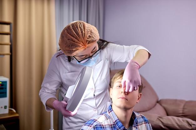 Cosmetologista examina pele de paciente do sexo masculino com sistema de equipamentos especiais de dermatologia, em consultório moderno. medicina e conceito de saúde da pele